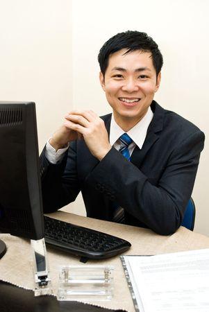 Asian business man at desk - smiling
