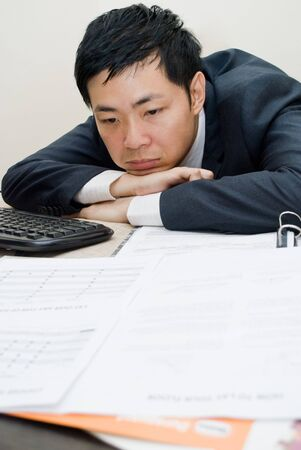 overwhelm: Asian businessman overwhelm with work - daydreaming Stock Photo