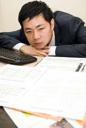 müdigkeit: Business Mann mit Kopfschmerzen an seinem Schreibtisch sitzen