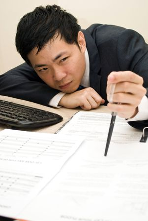 Asian businessman stabbing document photo