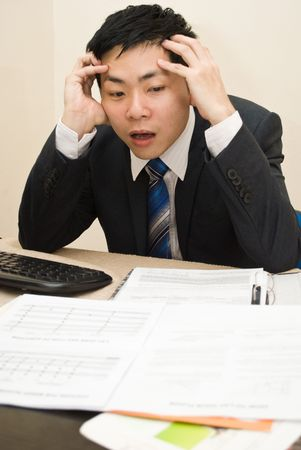 office force: Business man with headache sitting at his desk Stock Photo