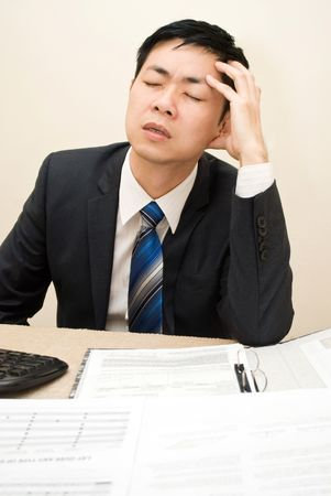 Business man with headache sitting at his desk Stock Photo