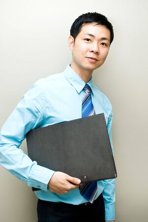 poised: Asian businessman carrying file