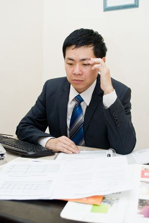 unhealthy thoughts: Asian businessman thinking and working