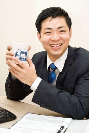 Asian business guy enjoying a mug of coffee Stock Photo - 5464460