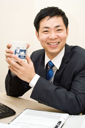 office force: Asian business guy enjoying a mug of coffee