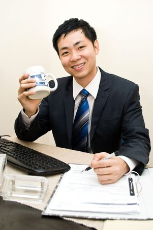 consumables: Asian business guy happy working with a mug of coffee