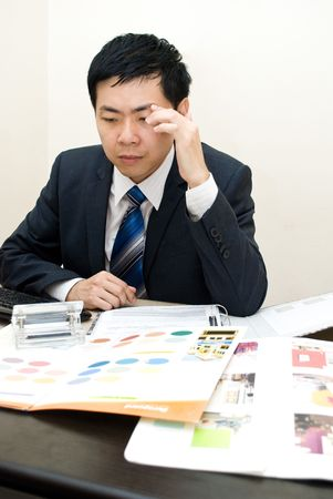 Tensed Asian businessman at work photo
