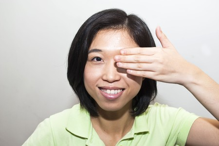Asian female cover eye with one hand photo