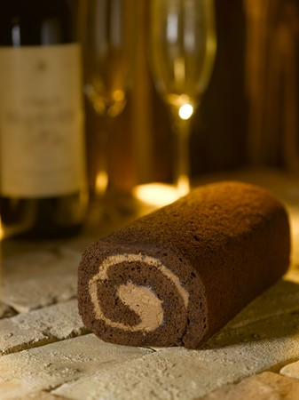 swiss roll: Swiss roll on brick with wine glasses and bottle Stock Photo