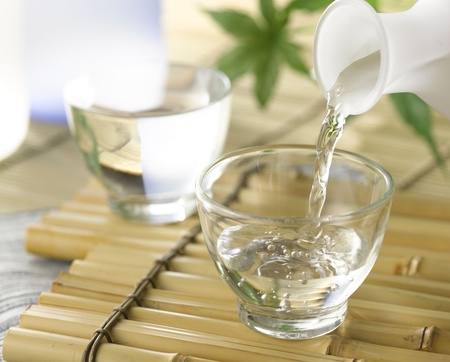 A cup of Japanese sake pouring from the sake decanter Stock Photo