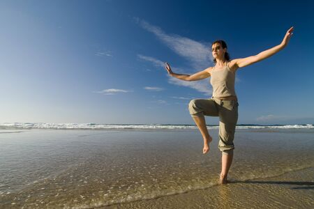 holydays: woman doing tai chi by the seashore in a sunny day