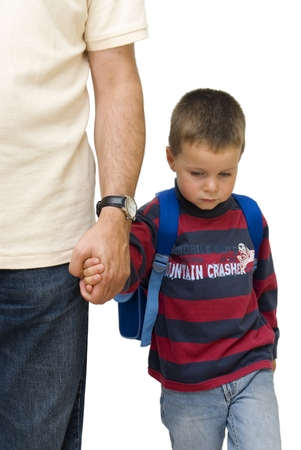 unhappy family: sad boy walking to school by his fathers hand