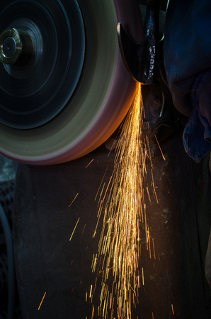 Industrial grinder showers sparks while working with metal. Stock Photo