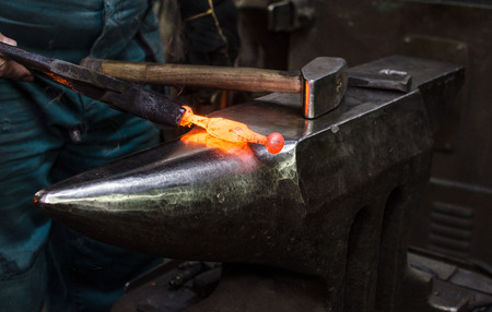 Blacksmith at work, hit with a hammer by a hot metal on the anvil. Banco de Imagens