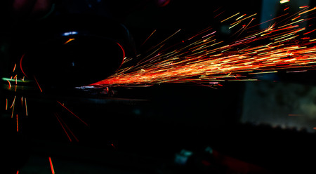 Industrial grinder showers sparks while working with metal. Archivio Fotografico