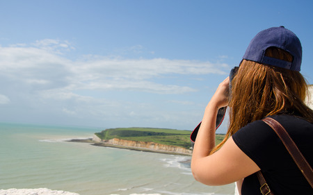 A tourist photographing the English coast with cliffs of seven sisters. Stock Photo