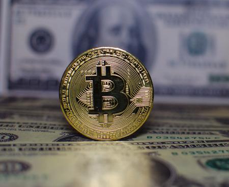 A virtual bitcoin coins versus dolars banknotes.