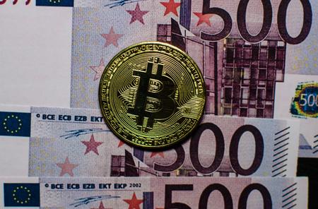 A virtual bitcoin coins versus euro banknotes.