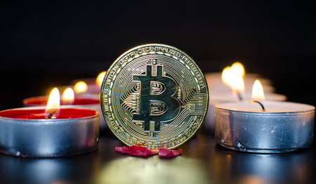 A virtual bitcoin coins with color candles. Imagens