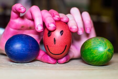 Painting easter eggs and dirty childrens hands.