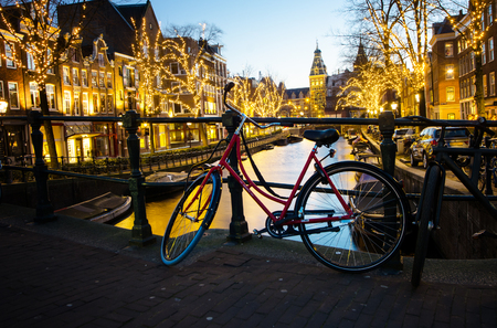 A classic red bicycle at night Amsterdam.