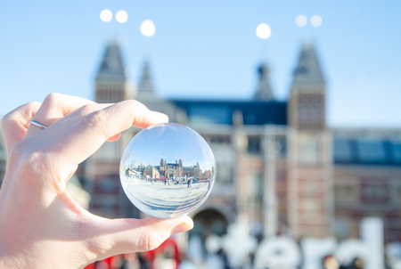 Amsterdam in glass ball on the hand. Stockfoto