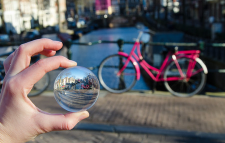 Pink bicycle in amsterdam in glass ball. Stockfoto