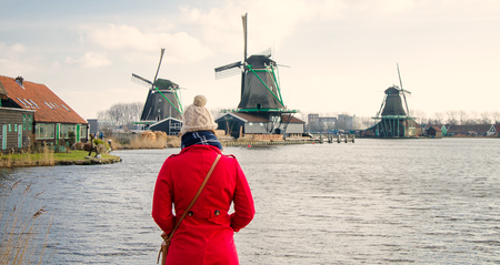 Woman in red coat looking at windmills in holland.