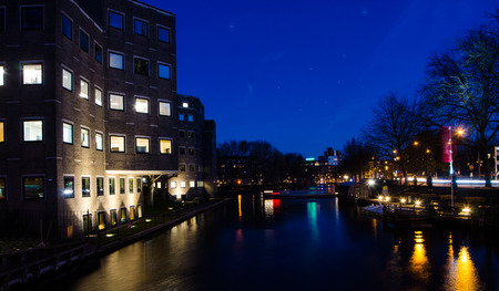 View of the classic canal in Amsterdam at night.
