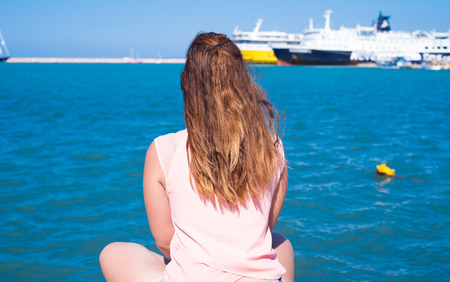 Woman sitting in a Greek harbor and looking at boats. Stock Photo