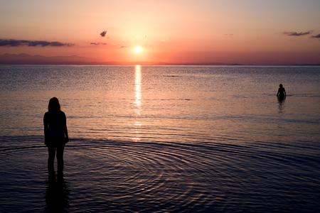 Women bathe in the sea at sunrise.
