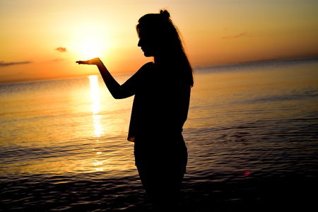 Woman playing with the sun on the beach in greece.