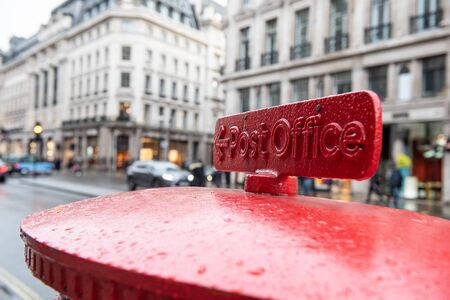 English red mailbox sending a letter in a busy London street.