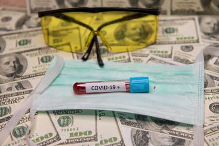 Dollars money and tube with blood and positive test at covid-19. 免版税图像