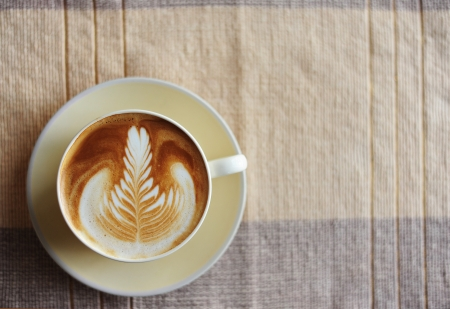 A cup of coffee with leaf pattern in a cup Stock Photo