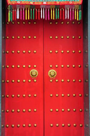 Red chinese door with a lion hand door