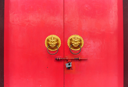 Red chinese door with a lion hand door photo