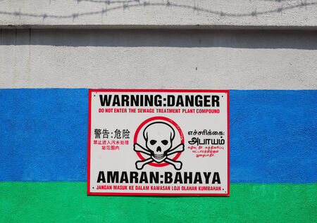 warning sign on wall and four languages English, Chinese, Tamil and Malay photo