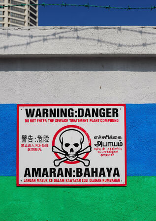 undermine: warning sign on wall and four languages English, Chinese, Tamil and Malay Stock Photo