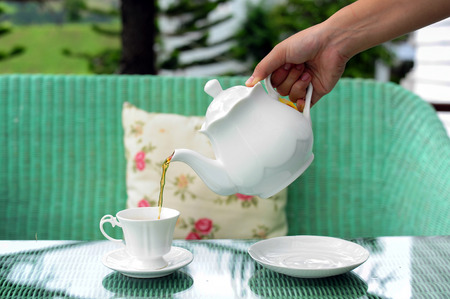 Pour tea from kettle into white cup photo