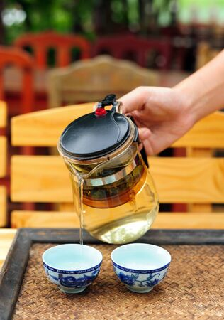 chinese tea cup: Pour tea from kettle into chinese tea cup