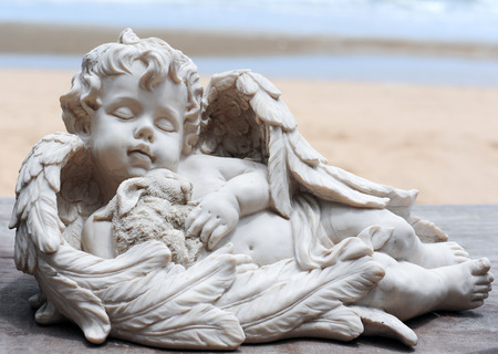 Ceramic angel and sea background photo