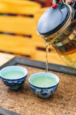 Pour tea from kettle into chinese tea cup photo
