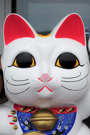 to beckon: Maneki Neko cat. Common Japanese sculpture bring good luck to the owner. Stock Photo
