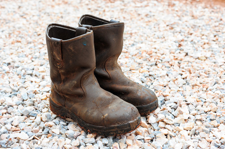 untied: old dirty boots.old boots worn with scratches and untied shoelaces on rock background Stock Photo