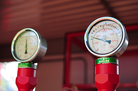 manometer: Closeup of manometer, measuring gas pressure. Pipes and valves on the background. Selective focus. Stock Photo