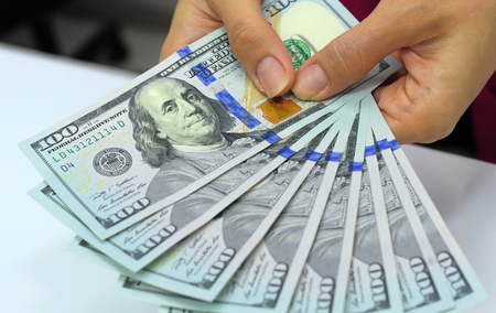 dollars: Cash in hands. Profits, savings. Stack of dollars. Woman counting money. Dollars in Womans hands. Woman in business clothes with dollars. Success, motivation, financial flows, wealth. Stack of dollars.