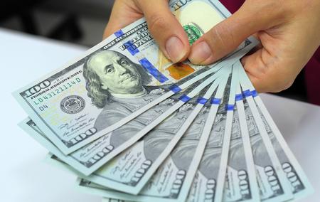 dollaro: Contanti in mano. I profitti, risparmi. Stack di dollari. Donna contando i soldi. Dollari in mani della donna. Donna nel commercio vestiti con i dollari. Successo, motivazione, i flussi finanziari, la ricchezza. Stack di dollari.