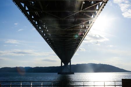 Kobe, Japan at Akashi Kaikyo Bridge in sunlight lens flair. The Akashi Kaikyo Bridge is, with a length of almost four kilometers, the worlds longest suspension bridge. Opened in 1998